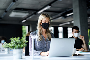 employees working on their computers with masks during the global pandemic