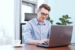 Young man with glasses typing on a laptop
