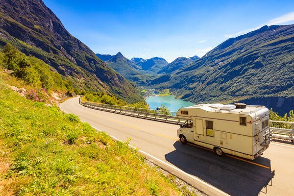 An RV is traveling down the road with a view of a crystal blue lake in the background. The lake is surrounded by mountains and valleys.