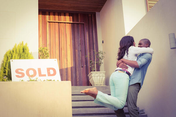 A woman and a man are hugging on the steps of a home. With a beautiful bamboo door and potted tree out front. A SOLD sign is placed in the foreground.