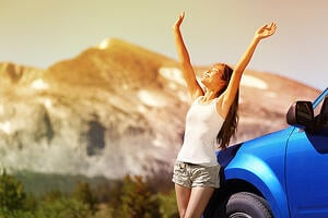 woman in the mountains happy standing next to a car