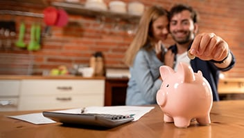 father and daughter putting money into a piggy bank
