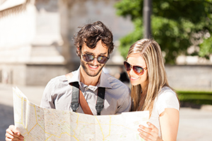 smiling couple with sunglasses looking at map