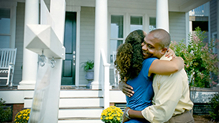 man and woman hugging on front porch