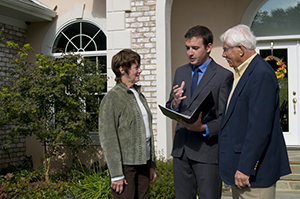 realtor talking to couple in front of house