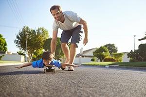 dad pushing son on skateboard