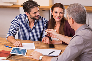 smiling couple meeting with realtor