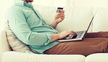 man using credit card on laptop