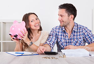 smiling couple with pink piggy bank of money