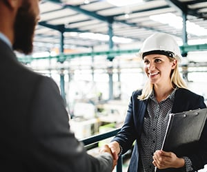 smiling man and woman shaking hands in manufacturing warehouse