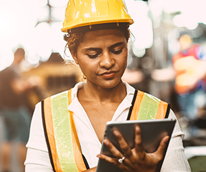 woman with hardhat and vest on tablet