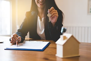 smiling woman handing over keys with paperwork