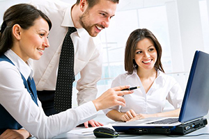 smiling employees reviewing benefits on computer