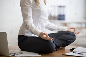 business woman sitting on her desk doing yoga