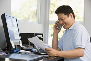 man smiling reviewing paperwork and on the phone