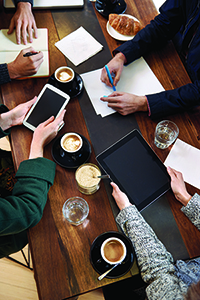 birds eye of business people on their smart devices drinking coffee