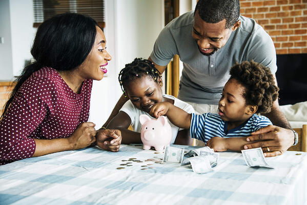 A family of four happily gather around a table where their young children place coins and dollar bills into a small pink piggy bank.