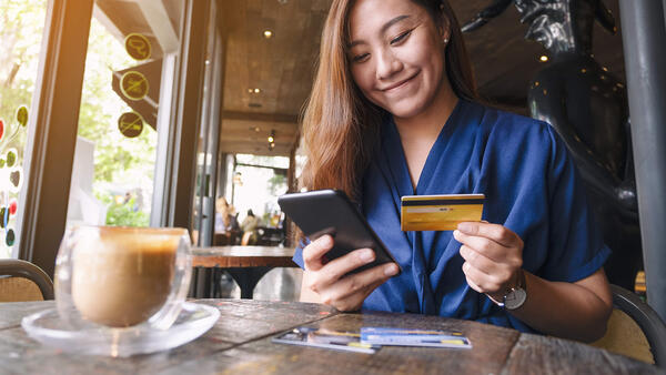 A well dressed woman smiles as she sits at a table with a cell phone in his right hand, and a credit or debit card in his left hand.