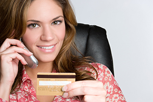 smiling woman on phone holding credit card
