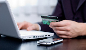 person using online banking holding credit card