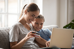 smiling woman and child using laptop and credit card