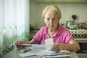 elderly woman grimly reviewing paperwork