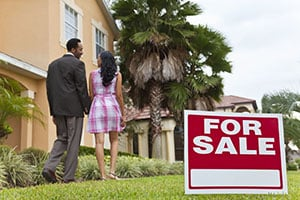 couple with their backs turned walking away from for sale sign