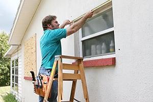 man preparing for hurricane by boarding windows