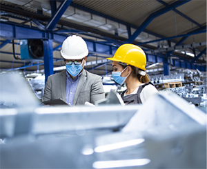 Man and woman with hard hats and masks working in a manufacturing plant