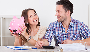 smiling couple with piggy bank of money