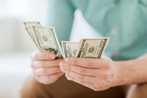 hands holding cash representing small business cash management