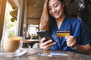 woman happily paying down debt on phone with credit card