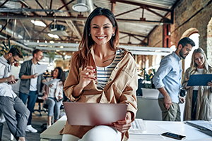 casual work office with woman smiling on laptop
