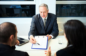 male banker going over business loan paperwork with couple