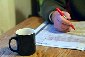 Man's hand reviewing newspaper with coffee cup