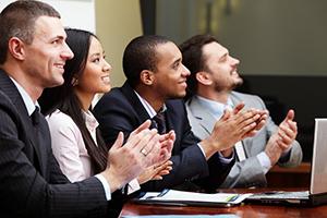 diverse business men and women applauding