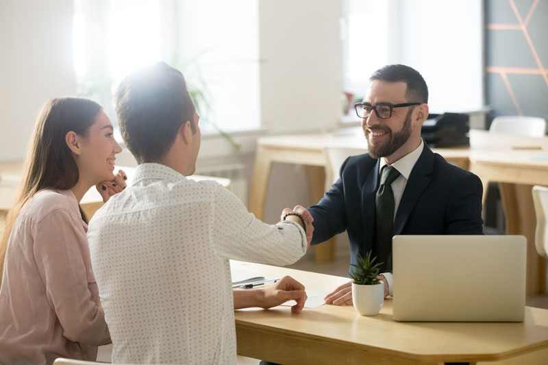 A young man and woman shake hands with a loan expert in his office.