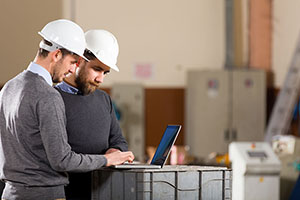 two men working on laptop with hard hats