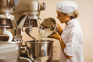 female baker mixing with large equipment