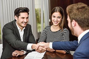 young couple happily working on paperwork with small business banker